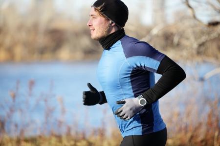 ropa de invierno: Hombre Runner en el otoño de correr en otoño con guantes y sombrero, escuchar música en auriculares. Coloque la formación atleta masculino fuera en un clima frío en los corredores cálido traje ropa. Modelo de la aptitud.