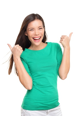 green thumb: Thumbs up happy excited woman isolated on white background in green t-shirt. Cheerful joyful and elated girl looking at camera. Multiracial Asian Caucasian girl in her twenties. Stock Photo