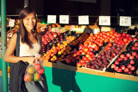 fruit stand: Woman buying fruits and vegetables at farmers market. Candid portrait of young woman shopping for healthy lifestyle. Multiracial Asian Caucasian female model. Stock Photo