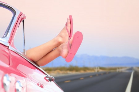 adult's feet: Freedom car travel concept - woman relaxing with feet out of window in cool convertible vintage car. Girl relaxing enjoying free holidays road trip.