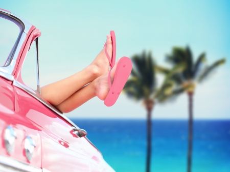 flip flops on the beach: Vacation travel freedom beach concept with cool convertible vintage car and woman feet out of window against tropical see background with palm trees. Girl relaxing enjoying free holidays. Stock Photo