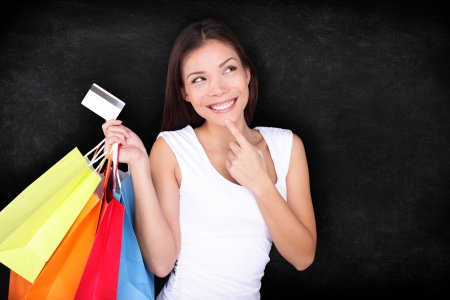 credits: Shopping woman thinking with bags on blackboard background. Shopper girl holding credit card and shopping bag looking up at blackboard  chalkboard background with copy space. Mixed race Asian model.