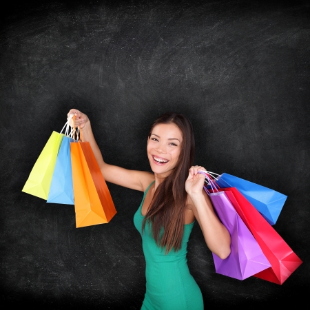 female clothing: Shopping woman holding shopping bags on blackboard background with copy space for your text or design. Happy excited female shopper showing purchases excited and joyful. Mixed race Asian girl