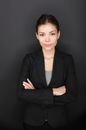 woman black background: Proud confident successful businesswoman portrait. Young business woman professional on black background with arms crossed looking at camera with confidence. Beautiful young mixed race Caucasian Asian