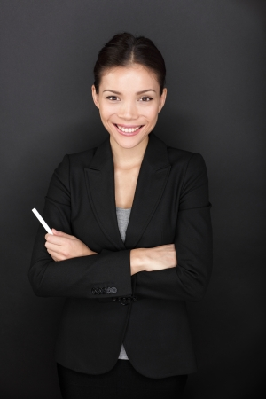 Teacher woman with chalk smiling happy portrait  Beautiful young female teacher holding chalk by blackboard  Teacher or business woman before lecture  Multiracial Asian Caucasian female model on black photo