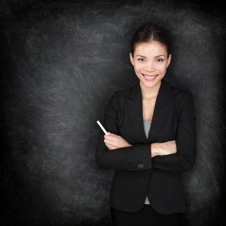 Woman teacher or business woman at blackboard holding chalk standing in suit by blackboard teaching or giving lecture  Young female professional portrait  Mixed race Asian Caucasian female model  photo