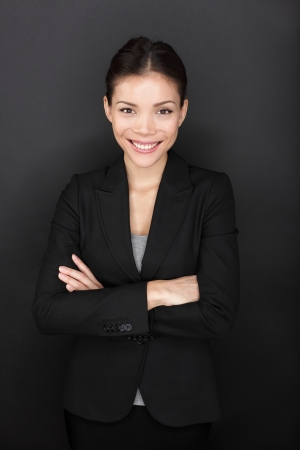 Businesswoman confident portrait Business woman standing proud with arms crossed smiling happy on black background looking at camera  Beautiful young professional mixed race Asian model in suit Stock Photo - 20836504