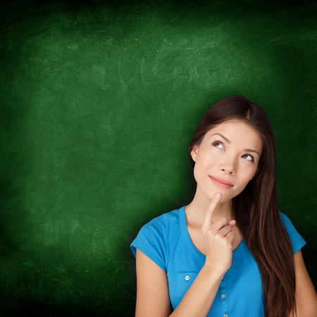 Thinking woman student or teacher with blackboard standing contemplative and pensive looking up to the side at empty green chalkboard copy space for your text or design  Multiracial Asian Caucasian  photo