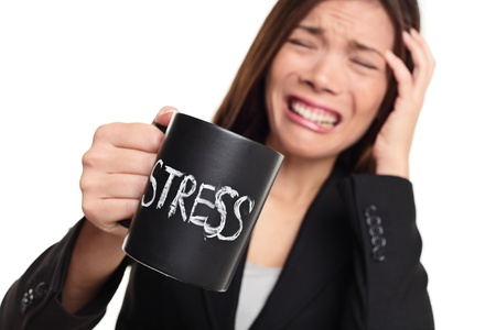 stressed: Stress at work concept  Business woman stressed being to busy  Businesswoman in suit holding head drinking coffee creating more stress  Mixed race Asian Caucasian female isolated on white background  Stock Photo