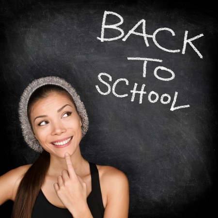 Back to school chalkboard - woman student thinking by blackboard  Female college university student girl thinking Back to School text  Modern trendy cool ethnic Asian Caucasian student in her 20s  photo