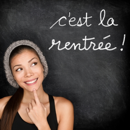 Cest la Rentree Scolaire - French college university student woman thinking Back to School written in French on blackboard by female on chalkboard  French language at college or high school  photo
