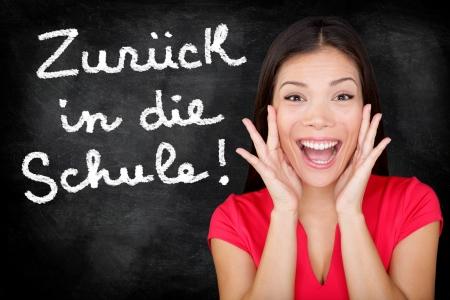 language school: Zuruck in die Schule - German student screaming happy Back to School written in German on blackboard by female teacher  Smiling happy woman teaching German language or university student in college Stock Photo