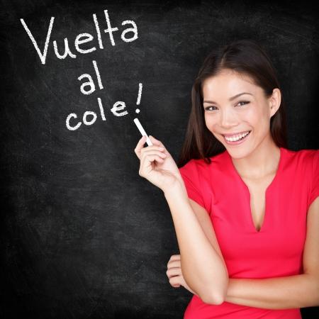 zpátky do školy: Vuelta al cole - učitel španělštiny Zpátky do školy písemně ve španělštině na tabuli by žena učitel drží křídu Usmívající se šťastná žena výuku španělského jazyka nebo vysokoškolské studenty zpátky ve škole Reklamní fotografie