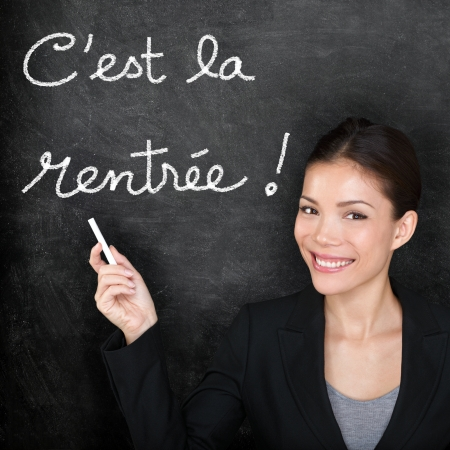 Cest la Rentree Scolaire - French teacher woman  Back to School written in French on blackboard  Female professor teaching French language at university, high shcool or primary school  photo