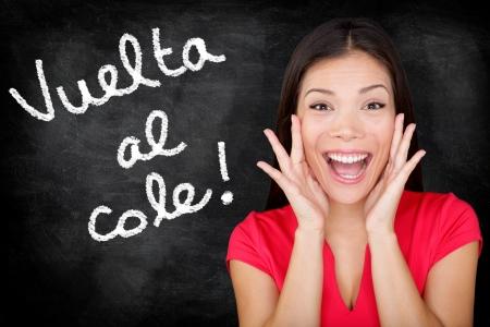 cole: Vuelta al cole - studente spagnolo urlando Back to School scritto in spagnolo sulla lavagna dall'insegnante donna. Sorride felice donna insegnamento della lingua spagnola o universit� studente al college. Archivio Fotografico