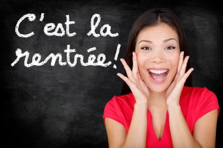 french text: Cest la Rentree Scolaire - French student screaming happy Back to School written in French on blackboard by woman teacher. Smiling happy female teaching French language or university college student