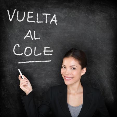 Vuelta al cole - Spanish teacher woman. Back to School written in Spanish on blackboard by female on chalkboard. Woman professor teaching Spanish language at university, high school or primary school. photo