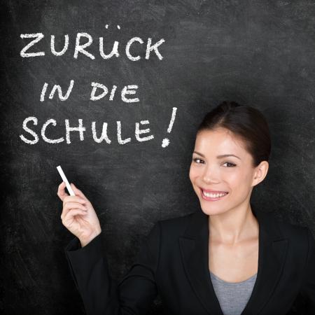 Zuruck in die Schule - German teacher woman. Back to School written in German on blackboard by female on chalkboard. Woman professor teaching German language at college, high school or primary school. photo