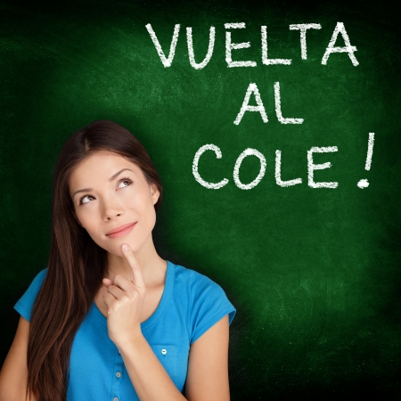 Vuelta al cole - Spanish college university student woman thinking Back to School written in Spanish on blackboard by female on green chalkboard. Spanish language at college or high school. photo