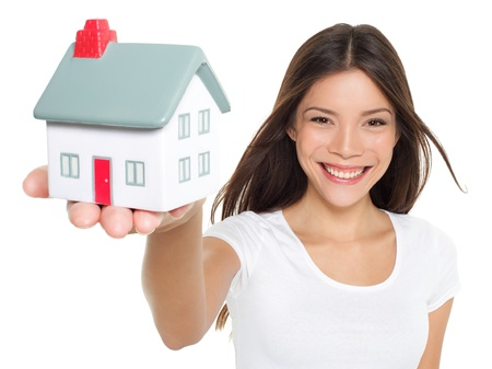 Home / house. Buying new home concept - woman holding mini house. House mortgage and happy home owner conceptual image with multi-ethnic Asian Chinese / Caucasian female model isolated on white background. Stock Photo - 20894601