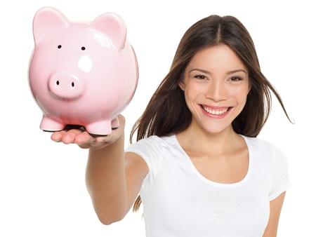 Piggy bank savings woman smiling happy. Female holding pink piggy bank isolated on white background. Multi-ethnic Chinese Asian  Caucasian girl. Banco de Imagens