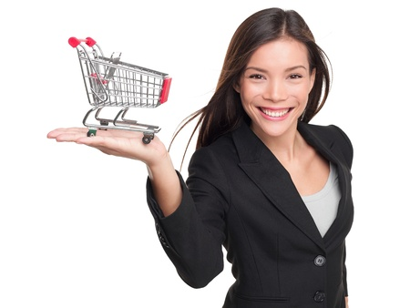 Shopping cart - business woman shopper. Woman showing holding mini shopping cart. Happy shopping or consumer loan concept with young female professional isolated on white background. photo