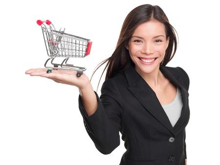 Winkelwagen - zakelijke vrouw shopper. Vrouw toont bedrijf mini winkelwagen. Gelukkig winkelen of consumptief krediet concept met jonge vrouwelijke professionele geïsoleerd op een witte achtergrond.