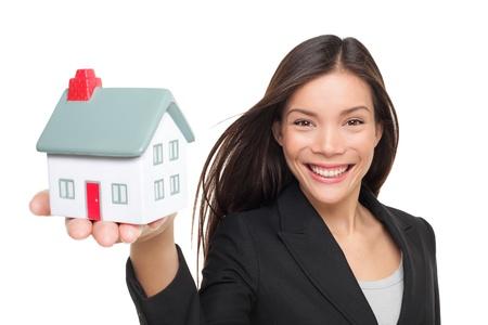Makelaar verkoopt huis bedrijf mini huis. Vrouwelijke makelaar in pak met model huis lachende gelukkige geïsoleerd op een witte achtergrond. Multiraciale Kaukasische  Chinese Aziatische vrouw middel.