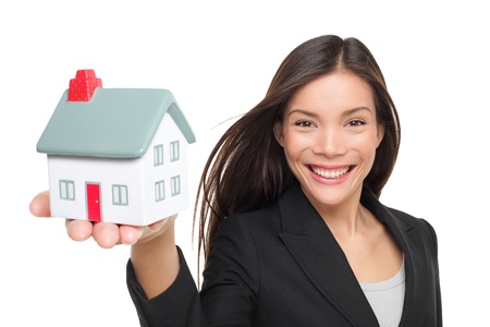 Real estate agent selling home holding mini house. Female realtor in business suit showing model house smiling happy isolated on white background. Multiracial Caucasian  Chinese Asian woman agent.