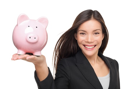 Businesswoman holding piggy bank - savings concept. Business woman or bank employee smiling happy. Female holding pink piggy bank isolated on white background. Multiracial Chinese Asian  Caucasian. photo