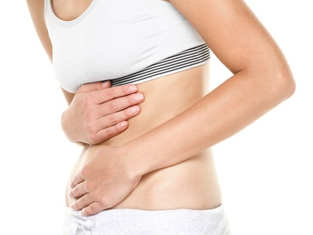 menstrual: Stomach pain. Woman having abdominal pain, upset stomach or menstrual cramps. Close up of young female model isolated on white background.