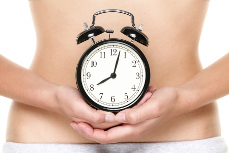 fertility: Biological clock ticking - woman holding clock in front of stomach. Biological clock and pregnancy concept with female hands and belly. Stock Photo