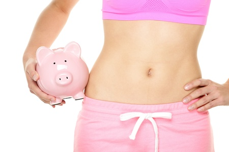 costs: Healthy fitness lifestyle is expensive. Fit woman holding piggy bank - healthy and fitness costs money concept. Close up of female stomach isolated on white background.