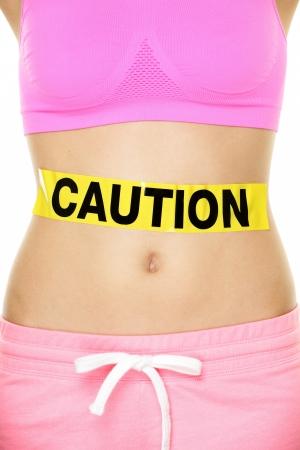 food poisoning: Stomach health concept showing woman belly CAUTION sign. Take care of your body, food poisoning or other concept. Conceptual healthy lifestyle image.