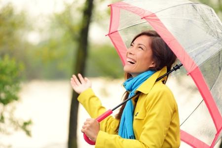 sotto la pioggia: Donna felice con ombrello sotto la pioggia in autunno foresta a piedi. Ragazza che gode del giorno di pioggia caduta la ricerca a cielo sorridente allegro. Mixed razza caucasica  asiatica ragazza cinese.