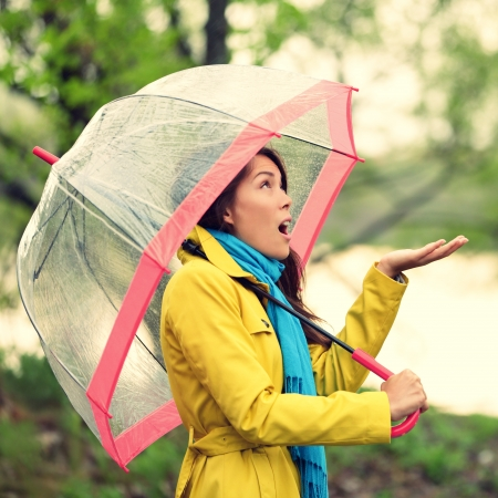 walking in the rain: Umbrella woman in Autumn excited under rain on fall day.Beautiful young female wearing raincoat surprised and excited in the rain. Mixed race Asian Caucasian girl in her 20s walking in forest. Stock Photo