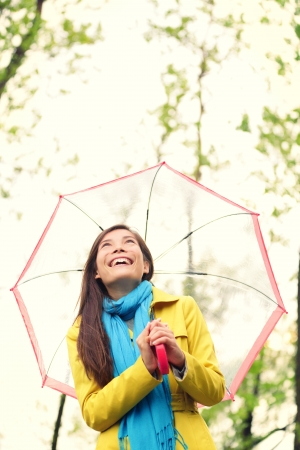 Asian woman in Autumn happy with umbrella in rain. Female model looking up at clearing sky joyful on rainy fall day wearing yellow raincoat outside in nature forest by lake. Mixed race Asian girl. Stock Photo