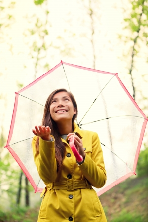 raincoat: Asian Autumn woman happy after rain walking with umbrella. Female model looking up at clearing sky joyful on rainy fall day wearing yellow raincoat outside in nature forest. Multiracial Asian girl.