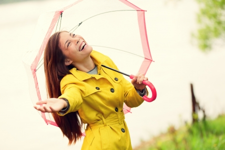 raincoat: Fall woman happy after rain walking with umbrella. Female model looking up at clearing sky joyful on rainy Autumn day wearing yellow raincoat outside in nature forest by lake. Mixed race Asian girl. Stock Photo