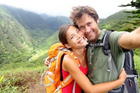 ハイキングのカップル - 恋にアクティブな若いカップル。カップルのハイキングにセルフ ポートレート写真を撮るします。男と女のハイカーはトレ 写真素材