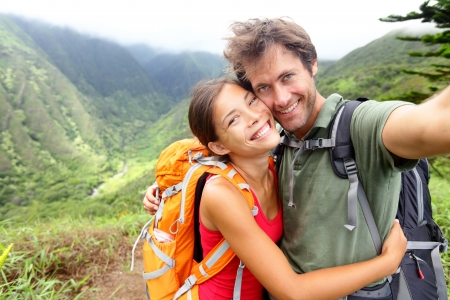 Hiking couple - Active young couple in love. Couple taking self-portrait picture on hike. Man and woman hiker trekking on Waihee ridge trail, Maui, USA. Happy romantic interracial couple. Banque d'images