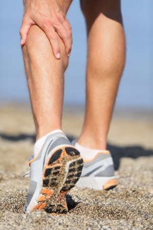 pulled: Muscle injury - Man running clutching his calf muscle after spraining it while out jogging on the beach. Male athlete sport injury.