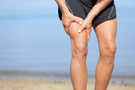 strain: Muscle injury. Man with sprain thigh muscles. Athlete in sports shorts clutching his thigh muscles after pulling or straining them while jogging on the beach.
