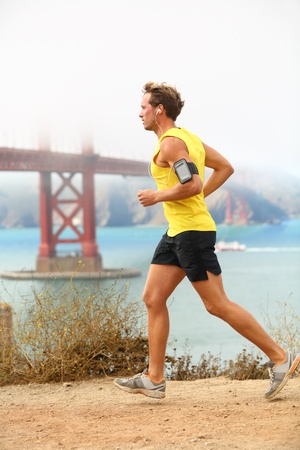 armband: Man jogging - male running in San Francisco. Sporty fit young man jogger along a dirt track alongside San Francisco Bay and Golden Gate Bridge. Runner listening to training music from smartphone. Stock Photo