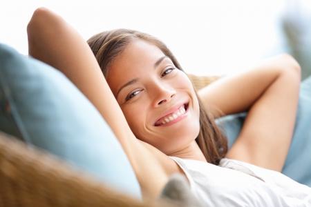 relajado: Mujer que se relaja se sienta c�modo en sill�n sof� sonriendo feliz mirando a la c�mara. Descanso bella joven multicultural ni�a cauc�sica asi�tica de 20 a�os. Foto de archivo