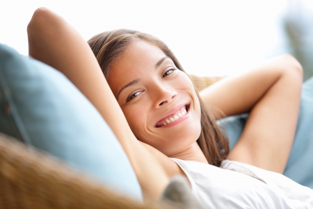 resting: Relaxing woman sitting comfortable in sofa lounge chair smiling happy looking at camera. Resting beautiful young multicultural asian caucasian girl in her 20s . Stock Photo