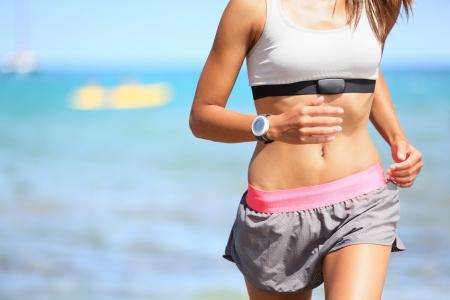 thể dục: Á hậu phụ nữ có theo dõi nhịp tim chạy trên bãi biển với chiếc đồng hồ và chiếc áo ngực thể thao hàng đầu. Đào tạo phù hợp với phụ nữ xinh đẹp mô hình tập thể dục và làm việc ra ngoài trong mùa hè tại một phần của lối sống lành mạnh.