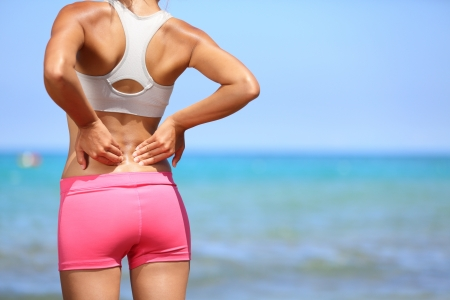 dolor de espalda: El dolor de espalda. Athletic mujer en ropa deportiva rosa de pie en la playa frotar los músculos de la espalda baja, recorta el retrato torso.