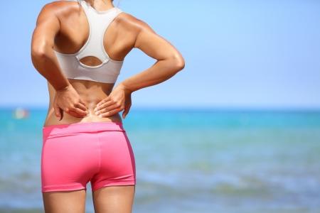 douleur main: Le mal de dos. Athletic femme en rose sportswear debout au bord de la mer se frottant les muscles du bas du dos, le torse recadr�e portrait. Banque d'images