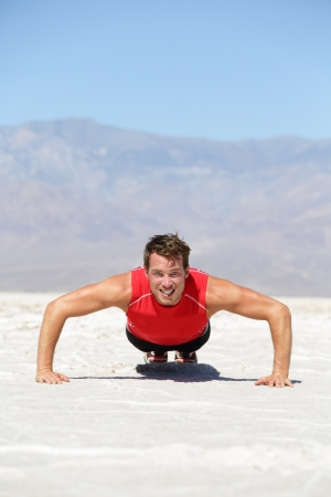 pushups: Fitness man crossfit training push-ups in death valley desert. Male athlete strength training outdoors in extreme nature landscape doing pushups. Fit male sport model in wearing compression t-shirt.